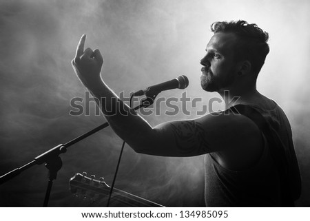 Young man gives finger to the audience. Play guitar.