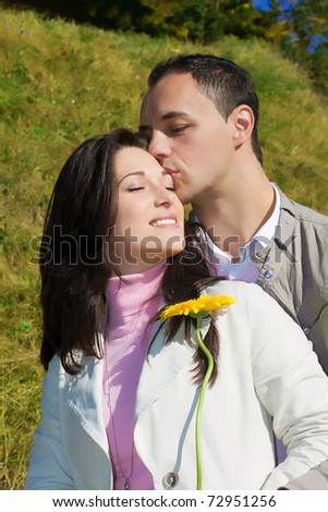 Young man giving a kiss to his love girlfriend outside on a sunny day - stock photo