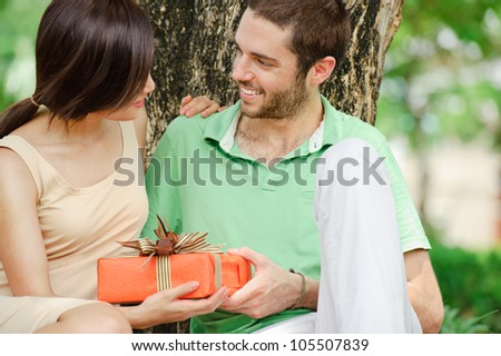 Young man giving a present to his girlfriend - stock photo