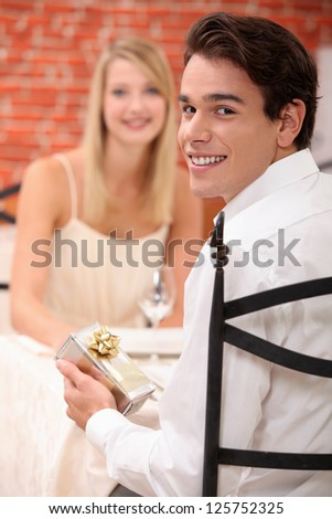 young man giving a present to his girlfriend at restaurant - stock photo