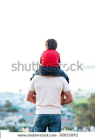 Young man giving child piggyback ride outdoors - stock photo