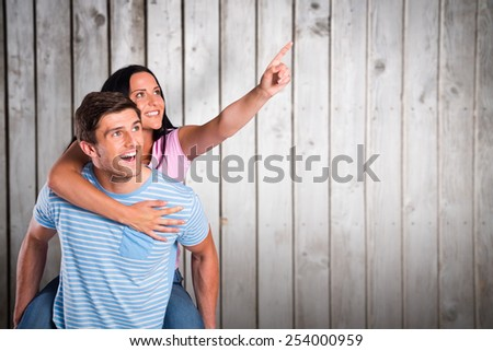 Young man giving girlfriend a piggyback ride against wooden planks - stock photo
