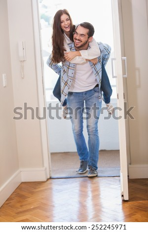 Young man giving girlfriend a piggyback ride in their new home - stock photo