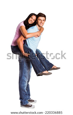 Young man giving girlfriend a piggyback ride on white background