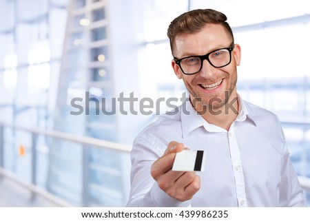 Young man giving his credit card looking at the camera - stock photo