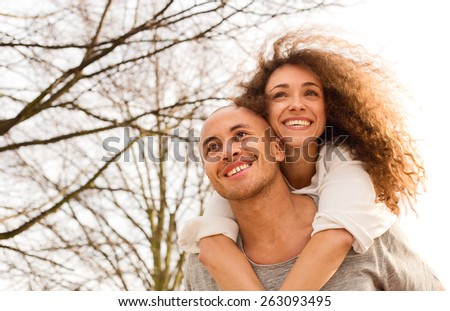 young man giving his girlfriend a piggyback - stock photo