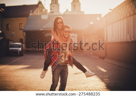 Young man giving piggyback ride to girl in town. naughty couple - stock photo