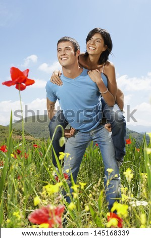 Young man giving piggyback ride to woman while looking away at poppy field - stock photo