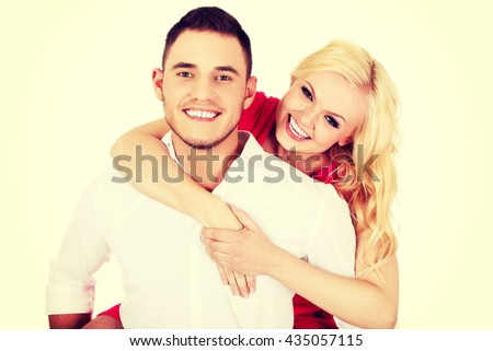 Young man giving piggyback to his girlfriend - stock photo