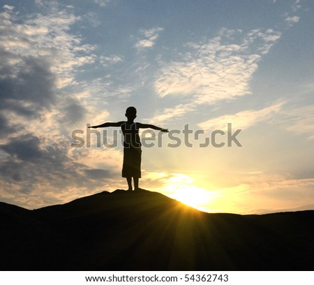 young man go up in sand desert in sundown silhouette - stock photo