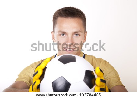 Young man goalkeeper holding a ball.