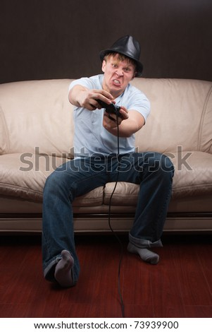 young man goes crazy while playing video games on gray background
