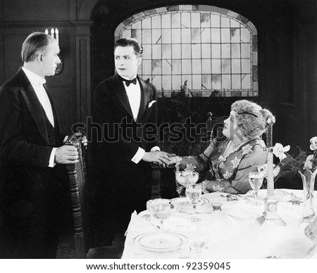 Young man greeting a couple at the dinner table