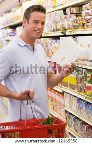 Young man grocery shopping in supermarket - stock photo