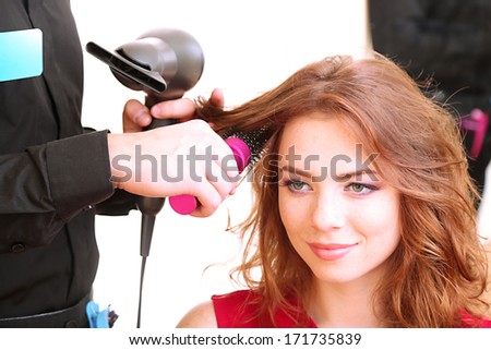 Young man hairdresser do hairstyle girl in beauty salon  - stock photo