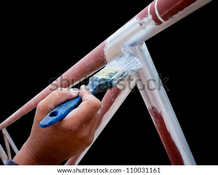 young man hand with flat tip paintbrush is  painting silver color to the metal structure tube frame isolated on black with working path - stock photo