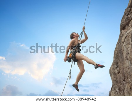 Young man hanging on a rope by a rocky wall over blue sky background