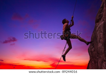 Young man hanging on a rope by a rocky wall over sunset sky background - stock photo