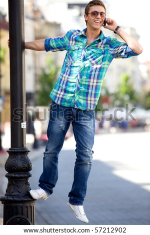 Young man hanging on lamp post - stock photo