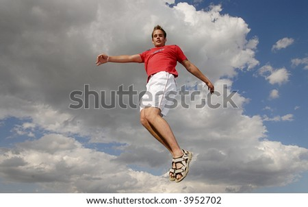 Young man happily jumping against blue sky.
