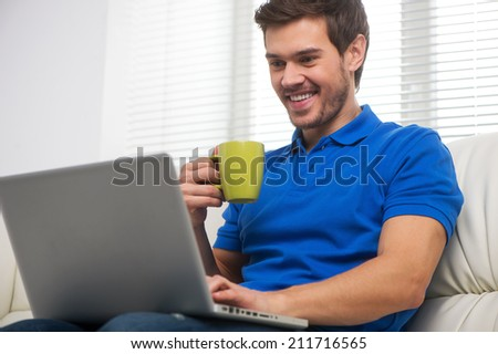 Young man happy on sofa with laptop. handsome male in t-shirt sitting on sofa and drinking - stock photo