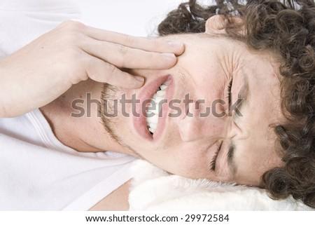 Young man has a headache - stock photo