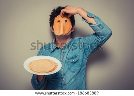 Young man has cut eyeholes in a pancake and is wearing it on his face - stock photo