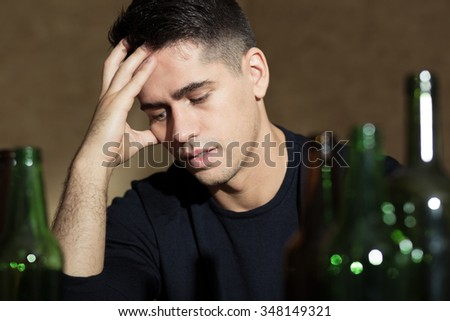 Young man has very big problem with alcohol - stock photo