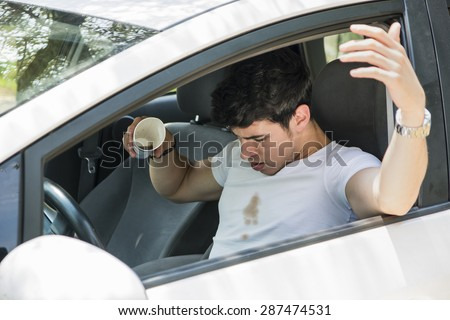 Young Man Having a Bad Day, Distracted Driver Looking Down in Frustration at Spilled Coffee on White T-Shirt While Sitting in Drivers Seat of Car - stock photo