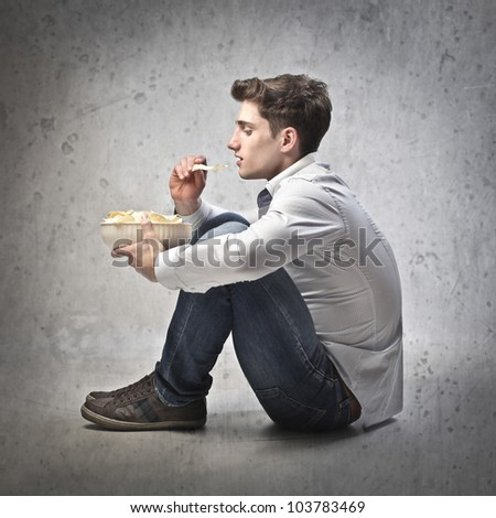 Young man having a bowl of chips - stock photo