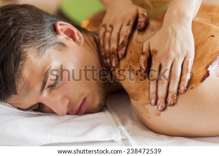 Young man having a hot chocolate massage - stock photo