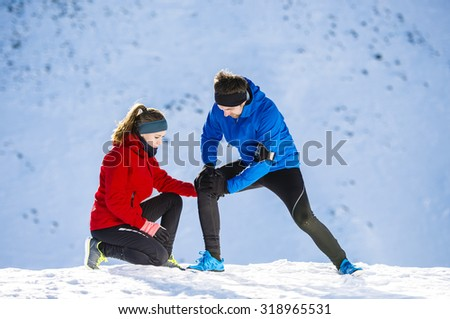 Young man having a knee injury while jogging outside in sunny winter mountains - stock photo