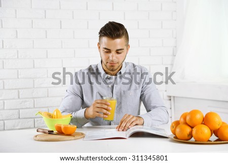 Young man having a table full of fresh oranges and juice