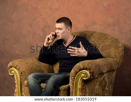 Young man having an animated conversation on his mobile phone as he sits in a comfortable armchair gesticulating with his hands - stock photo