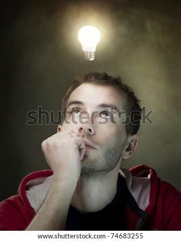 Young Man Having an Idea. Light bulb above his head - stock photo