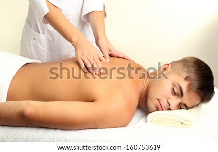 Young man having back massage close up - stock photo