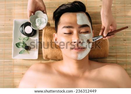 Young man having beauty treatment in spa salon - stock photo