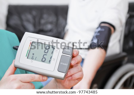 Young man having blood pressure check at home. He is in wheelchair.