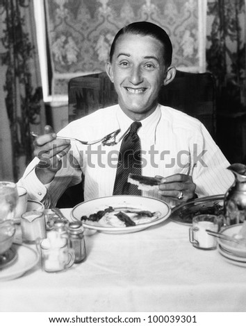 Young man having breakfast and smiling - stock photo
