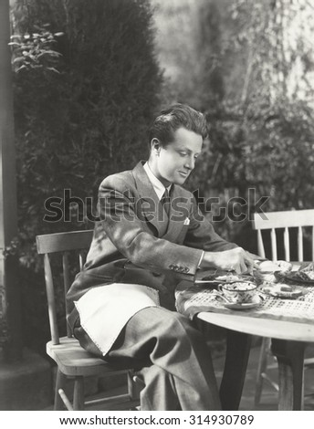 Young man having breakfast at outdoor table