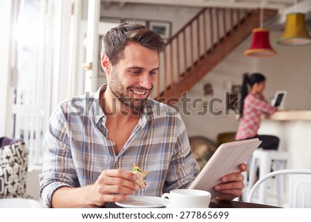 Young man having breakfast in a cafe - stock photo