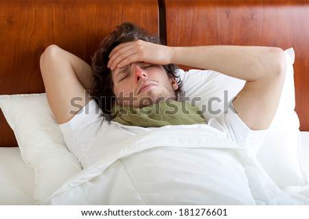 Young man having cold lying in bed, horizontal - stock photo