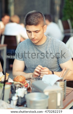 Young man having double cheeseburger in outdoor restaurant