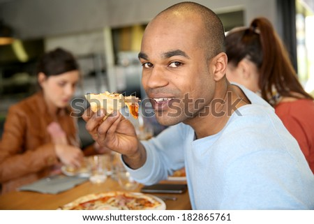 Young man having eating pizza slice  - stock photo