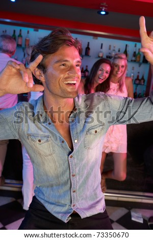 Young Man Having Fun In Busy Bar - stock photo