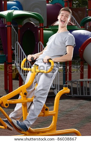 Young man having fun on a fitness machine - stock photo