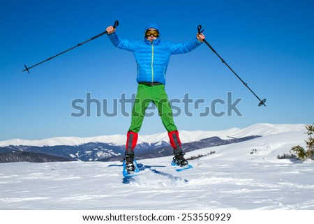Young man having fun while snowshoeing outdoors on a lovely snowy winter day. - stock photo
