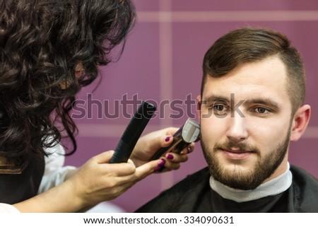 Young man having his beard groomed at barbershop - stock photo