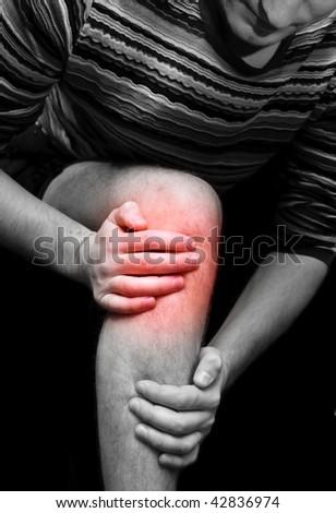 Young man having knee ache - stock photo
