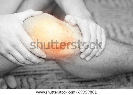 Young man having knee pain - stock photo